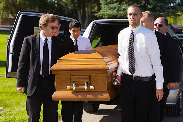 A group of men carrying a casket in a funeral.